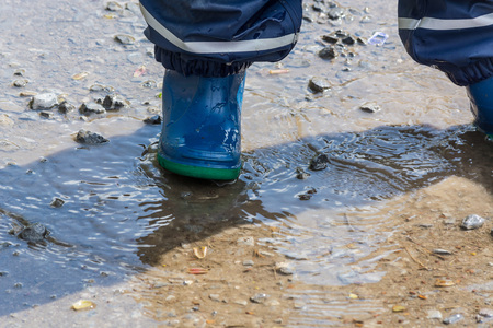 drench: Child with blue rubber boots in a puddle. close up view