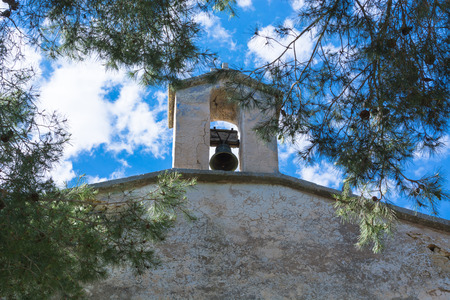 spanish style: Church tower with bell in Spanish style against a blue sky. Stock Photo