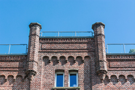 House facade of a typical old brick house against blue sky.