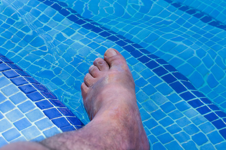 Men feet in a beautiful swimming pool with blue tiles. Stock Photo