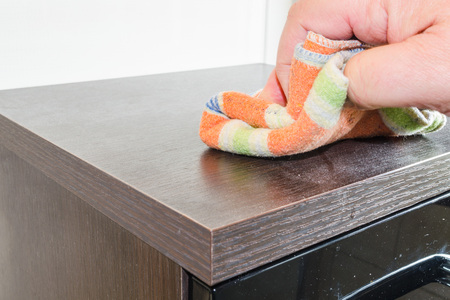 putz: Wiping a dusty cabinet with wooden surface with a cleaning cloth. Stock Photo