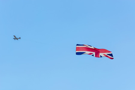 writable: Banner towing, small engine aircraft towing banners for advertising.Here the flag of Great Britain.