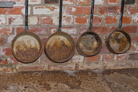 ladles: Old rusty foundry ladles hanging on a wall of bricks.