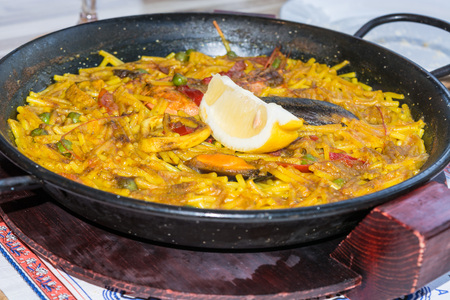 marisco: Gourmet Valencia paella with seafood and fresh lobster, calamari and mussels with saffron rice and lemon slices, closeup.