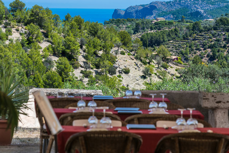 secretive: Focus on background.Tables and chairs of a romantic secretive restaurant on the coast of the Iceland of Mallorca, Spain.