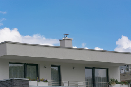 Floor of a modern residential building in bungalow style with a flat roof against blue sky.
