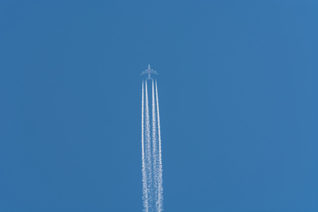 business life line: Aircraft flying at high altitude contrails against a dark blue sky.