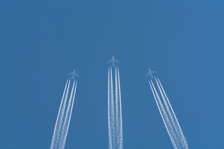 business life line: Three planes flying at high altitude. Contrails against a dark blue sky.