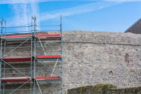Old city walls with scaffolding against blue sky. Stock Photo