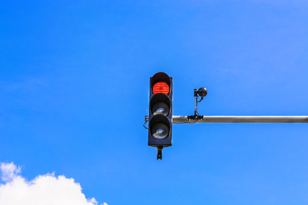 violation: A traffic light and a surveillance camera on a pole mounted on the street.