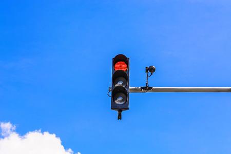 Een verkeerslicht en een bewakingscamera op een paal gemonteerd op de straat.