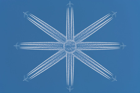 Eight aircraft at high altitude flying in star-shaped formation. Contrails against a dark blue sky.