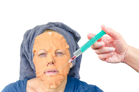 european ethnicity: Close-up portrait of a cosmetic face mask and an injection with botulinum toxin in the female face lip zone. Stock Photo