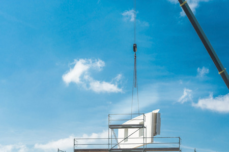 A wall part of a prefabricated house on a crane against blue sky.