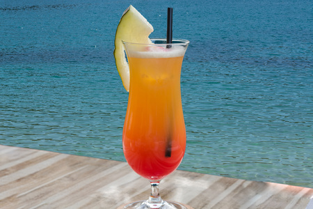 beardless: Colorful cocktail on the table of a bar in the restaurant in the background the blue sea. Stock Photo
