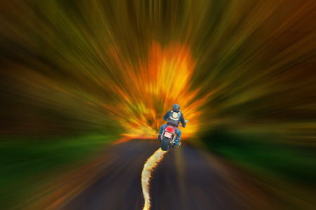 fraternity: Motorcyclist with burning tire against a blurred abstract background.