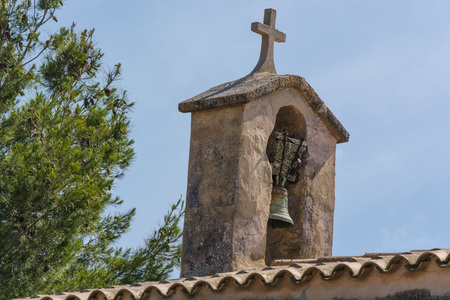 Church tower with bell in Spanish style against a blue sky. Stock Photo