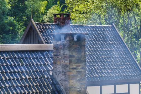 housetop: Smoking chimney on the roof of a house.