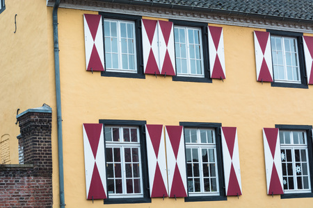 run down: Facade of the county museum Zons in Germany on the Rhine. House front with red and white window shutters.