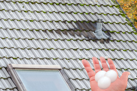 Severe damage to the roof by hail. Human hand with hail grains in front of a building roof.