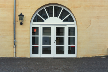 rungs: New large round arch door with rungs in a yellow plastered house wall.