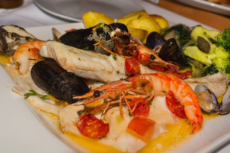 calamares: Varied seafood, dorade, mussels and shrimps on a white plate.
