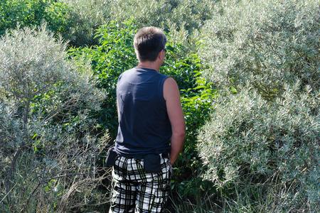 Hombre orinando en los arbustos durante una caminata.
