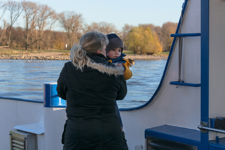 commercially: Mature woman with child on the Rhine ferry near Dormagen Zons in Germany. Stock Photo