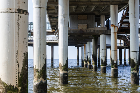 Concrete piers, concrete columns protrude from the water at the pier of Scheveningen in the Netherlands.