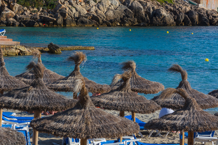 Blue sea and sand beach with sun loungers and parasols. Stock Photo