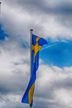 Swedish country flag arranged against a blue sky.