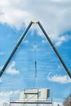 partitions: Two mobile construction cranes when delivering a prefabricated building. Concrete wall against blue sky. Stock Photo