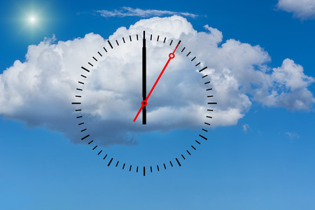 Clock, dial with a minute hand and a red second hand indicates 12 o'clock. Copy space in front of sky and cloud background.