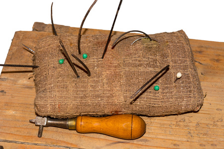 Shoemaker tool, accessories sewing needle, scissors and thread on linen cushion.