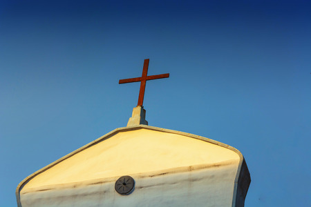 attic: Front view of a mediterranean church, on the roof of a cross. Stock Photo