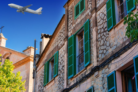 Buildings in the village of Valldemossa on the island of Majorca in Spain. In the background in the sky a passenger airplane.