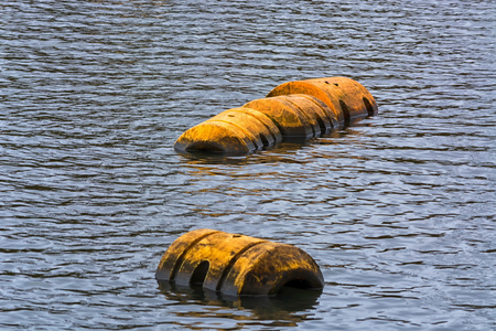 Buoy, pipeline or plastic floats float on the water surface.
