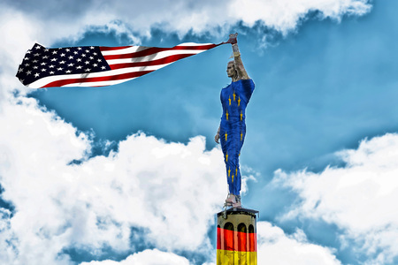 Antique stone statue wrapped in a European flag holding a USA flag, American national flag in hand. The stone base on which the statue stands is painted in German national colors. Stock Photo