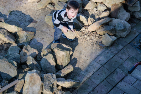skimming: Little boy throwing a stone into a water barrel