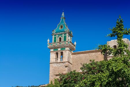 Beautiful view. Tower of the Monastery of Valldemossa in the Sierra de Tramuntana Mountains with park. Stock Photo