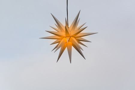 Lighted Christmas star on a background with color gradient in pastel colors. Standard-Bild