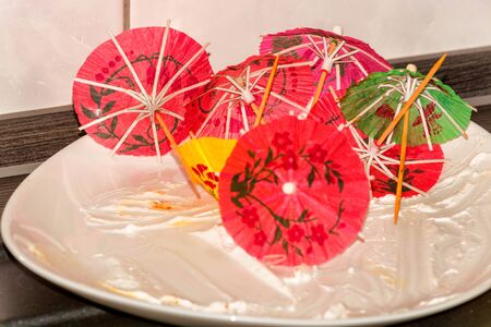 spanned: Empty white cake plate, plate on a kitchen plate with colorful paper decoration umbrella.