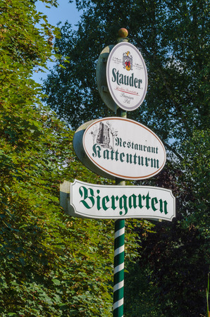 ESSEN, NRW, GERMANY - JULY 23, 2014:  Advertising Sign in Essen district of Kettwig near the restaurant at the Kattenturm. Green and white striped wooden post with advertising surface.