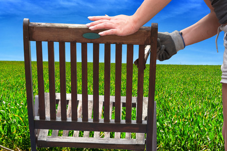 painted wood: Painting and applying protective eco-friendly paint on a wooden garden chair.