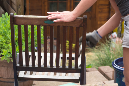 painted wood: Painting and applying protective varnish on a wooden garden chair