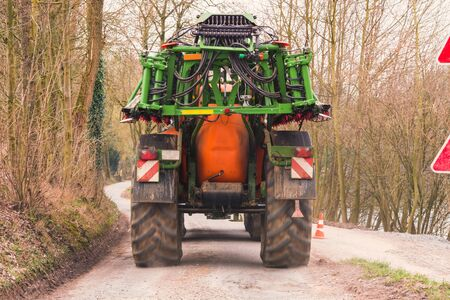 Tractor with Agricultural machine for spraying fertilizers or insecticides on a field. Stock Photo