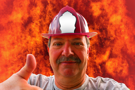 Portrait of a firefighter with helmet, fire in the background a flame sea. Stok Fotoğraf