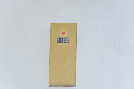 白い外壁の温度計は 30 度を示しています。夏の暑い日の概念。