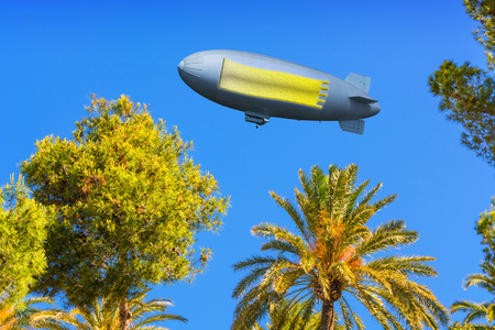 Landscape, tree tops of pines and palm trees on the Mediterranean Sea on Mallorca in Spain. In the sky a zeppelin with banner, copy space.