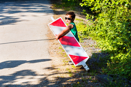 Little boy is carrying a construction site barrier across the street. To overcome difficulties